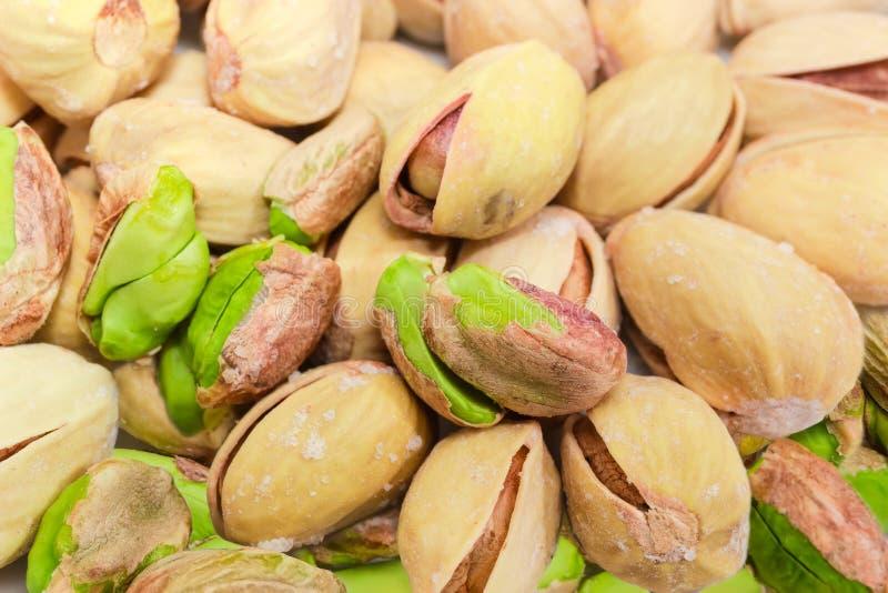 De gedeeltelijk gepelde geroosterde gezouten close-up van pistachenoten bij selectief stock afbeeldingen