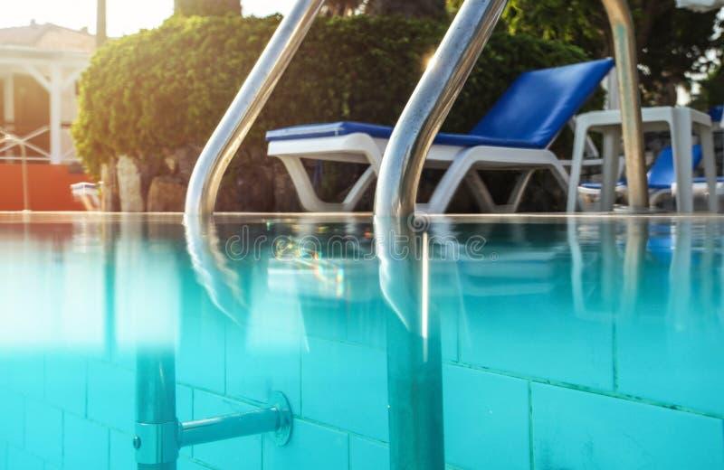 De gedeeltelijk onderwaterfoto, staalleuningen bij ingang aan zwembad, backlight zont het glanzen op achtergrond De vakantie/onts royalty-vrije stock foto's