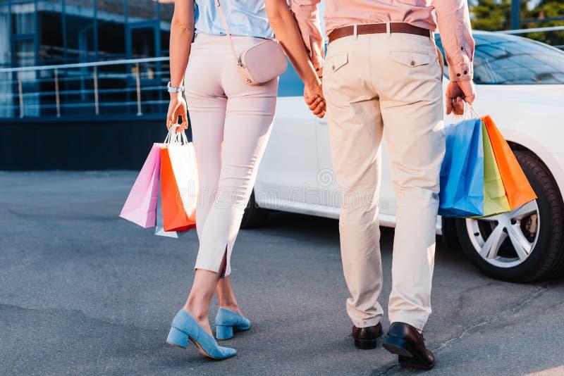 de gedeeltelijke mening van echtpaar met het winkelen doet het houden van handen in zakken terwijl het lopen aan auto royalty-vrije stock afbeelding