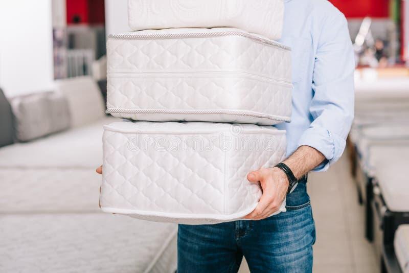 de gedeeltelijke mening van de stapel van de mensenholding van het vouwen van matrassen dient binnen meubilairopslag in royalty-vrije stock afbeelding