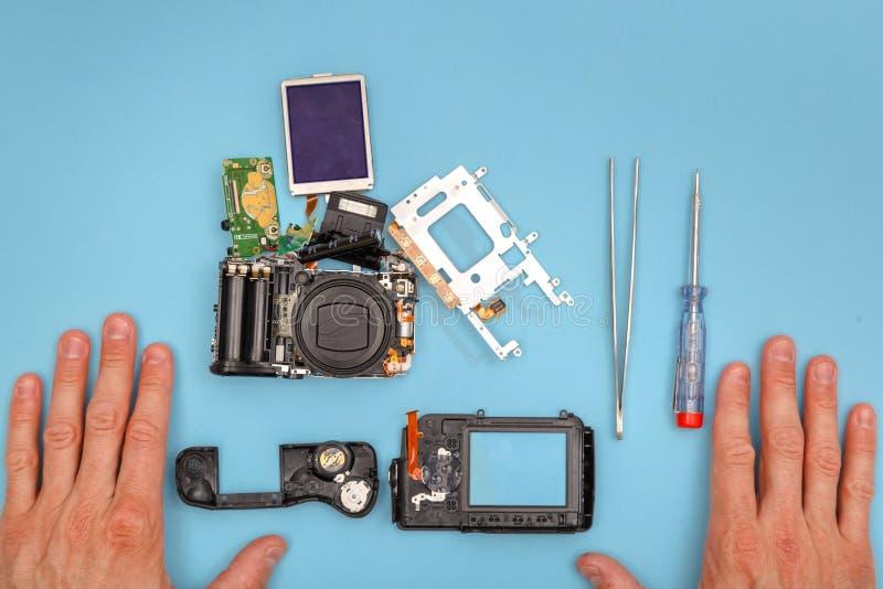De gedemonteerde camera, hulpmiddelen en handen van de hersteller royalty-vrije stock foto's