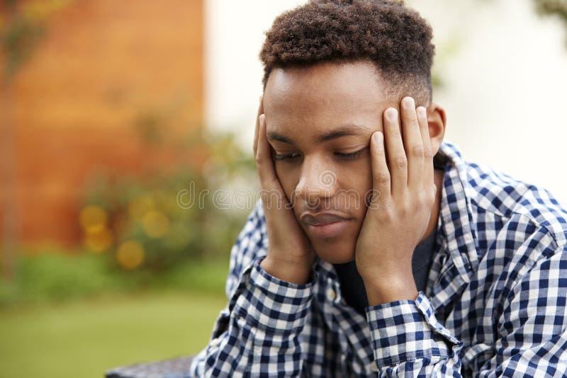 De gedeprimeerde jonge Afrikaanse Amerikaanse mens met hoofd in handen, sluit omhoog, leidt en schouders royalty-vrije stock foto's