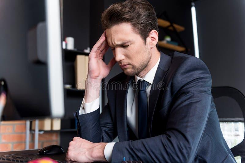De gedeprimeerde jonge mens heeft hoofdpijn royalty-vrije stock fotografie