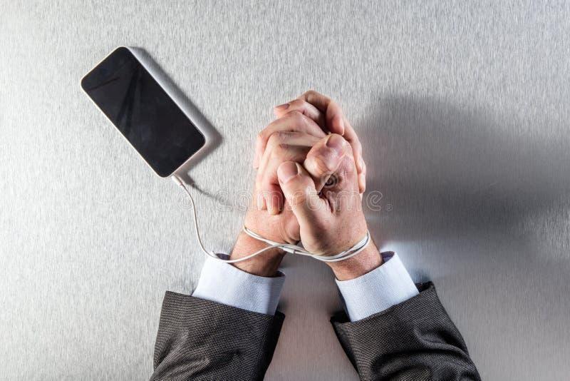 De geduldige handen van de werkverslaafdezakenman vast aan zijn mobiel telefoonkoord stock foto's