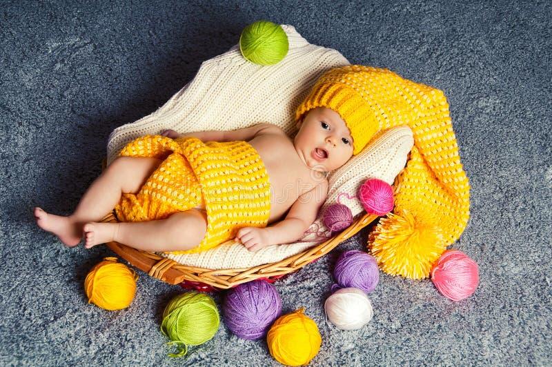 De geeuwende baby ligt in een mand. Rond garen voor het breien. stock afbeelding