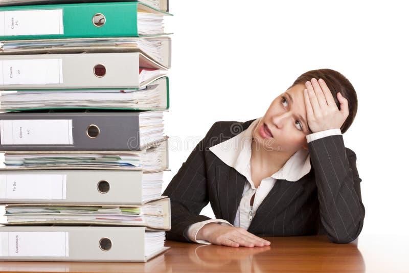 De gefrustreerde bedrijfsvrouw bekijkt omslagstapel stock afbeelding