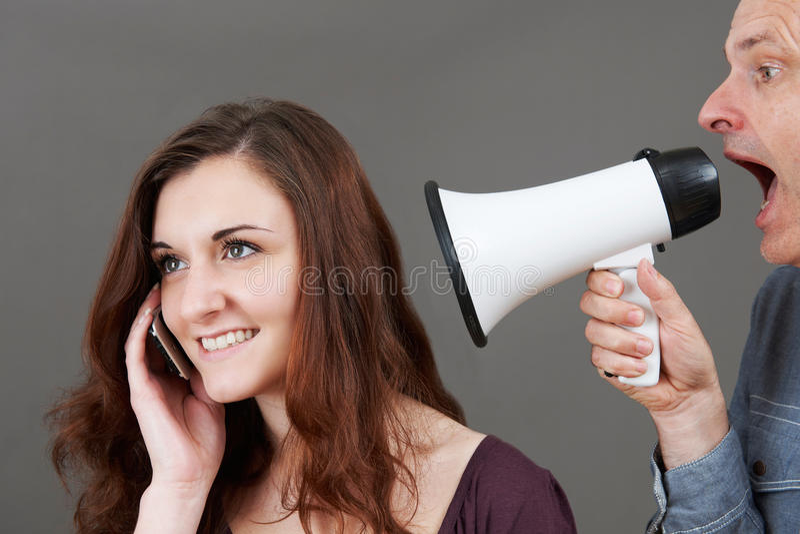De gefrustreerde Dochter van Vadershouting at teenage op Mobiel door stock fotografie