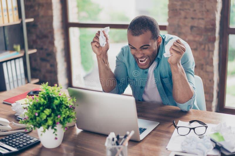 De gefrustreerde jonge Afrikaanse ondernemer schreeuwt bij zijn laptop in bureau en belemmert de documenten Hij is boos wegens gr royalty-vrije stock afbeeldingen