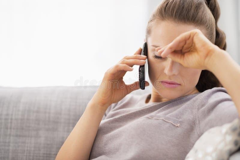 De gefrustreerde jonge telefoon van de vrouwen sprekende cel royalty-vrije stock afbeelding