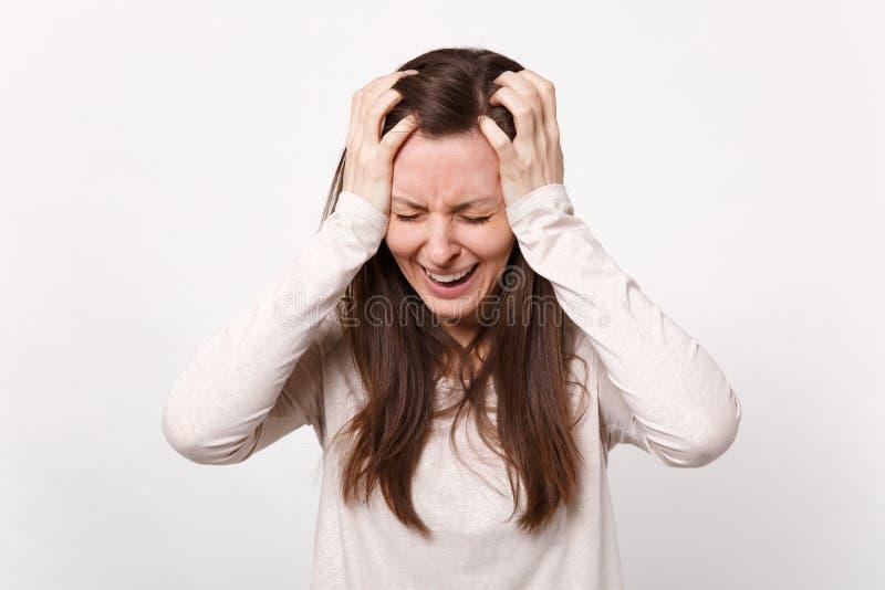 De gefrustreerde schreeuwende ontevreden jonge vrouw in lichte kleren die ogen houden sloot, zettend handen op hoofd dat op wit w stock afbeelding