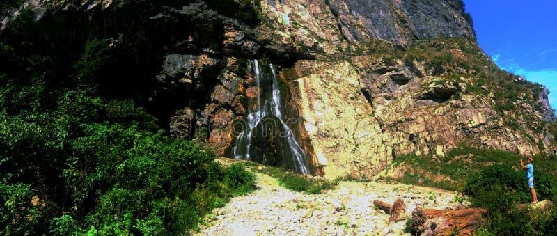 De Gega-waterval Een mens fotografeert de grootste waterval in Abchazië op een zonnige de zomerdag stock afbeelding