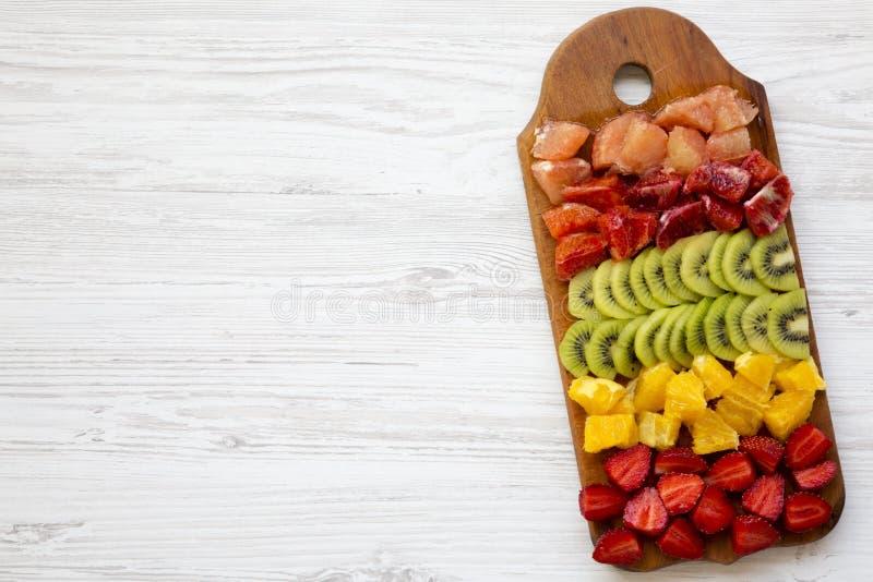 De gehakte verse vruchten schikten op scherpe raad op witte houten achtergrond met exemplaar ruimte, hoogste mening Ingrediënten  stock afbeeldingen