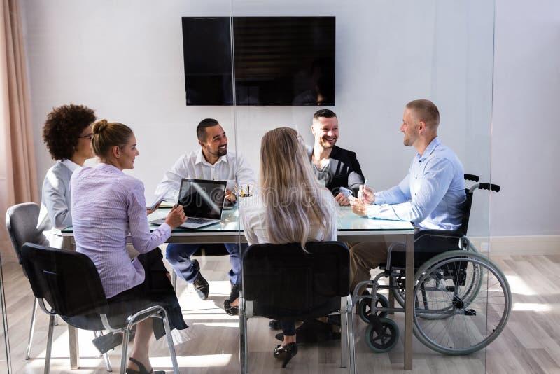 De gehandicapte Collega's van Managersitting with his royalty-vrije stock afbeeldingen