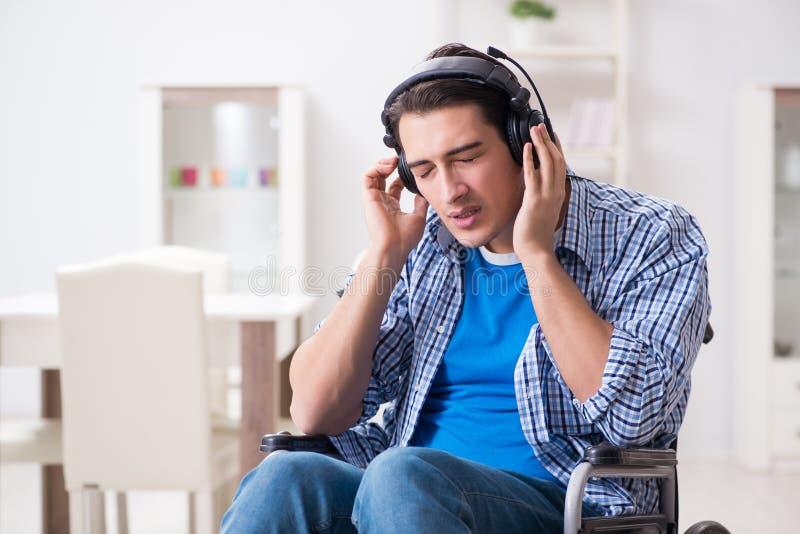 De gehandicapte man die aan muziek in rolstoel luisteren stock foto