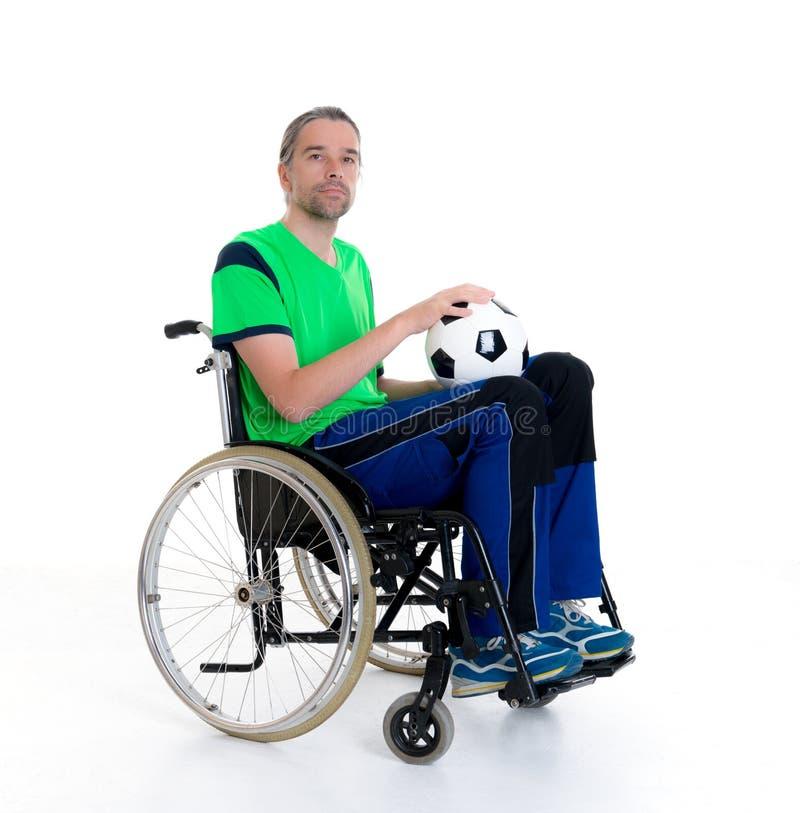 De gehandicapte mens in een rolstoel doet sport met bal royalty-vrije stock afbeelding