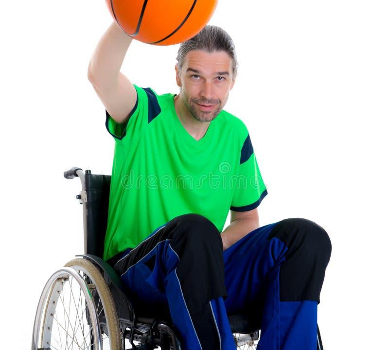 De gehandicapte mens in een rolstoel doet sport met bal stock afbeeldingen