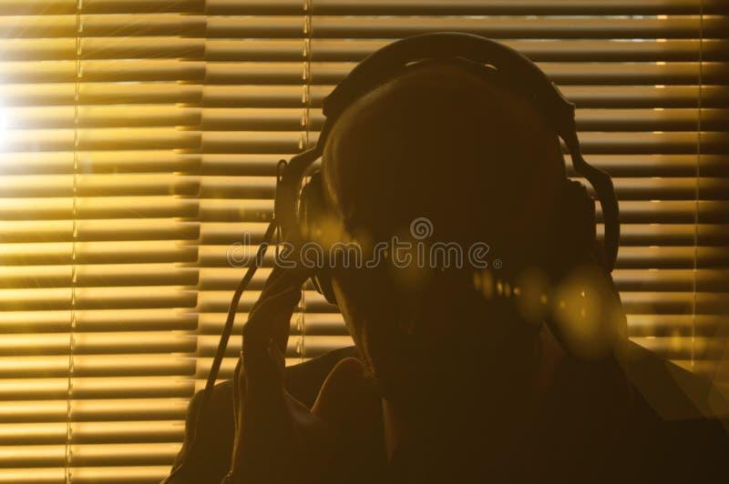 De geheimagent luistert een gesprek in hoofdtelefoons op de achtergrond van het venster met zonneblinden, zonglans en het stemmen stock foto