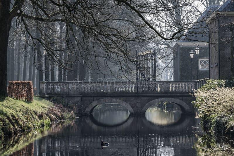 De geheimzinnige brug dacht in water op een mistige ochtend in Laren, Nederland na royalty-vrije stock fotografie