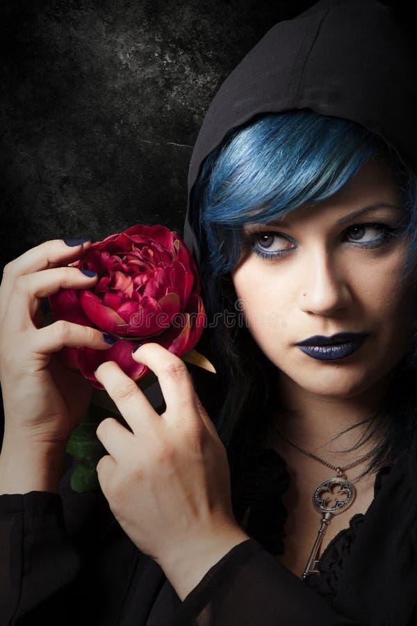 De geheimzinnige jonge vrouw met rood nam toe Blauw haar stock foto