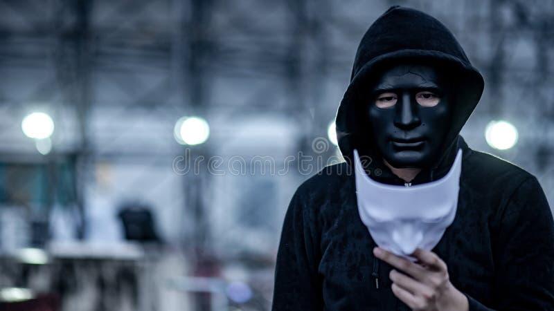 De geheimzinnigheid hoodie bemant met gebroken zwart masker die wit masker in zijn hand houden Het anonieme sociale maskeren of b royalty-vrije stock afbeelding