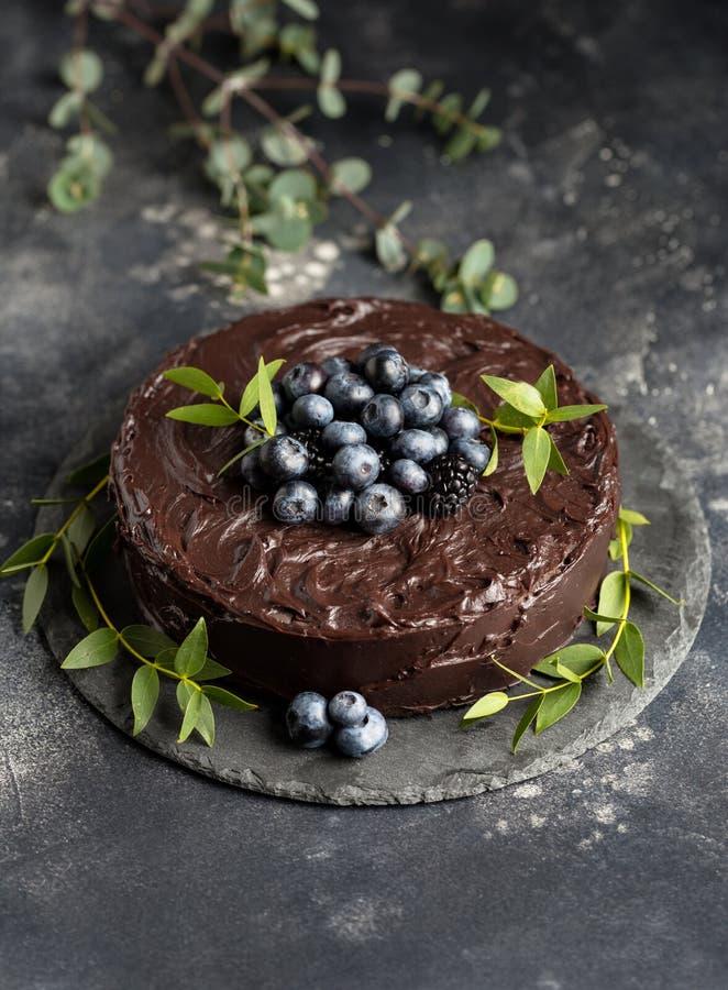 De gehele chocoladecake met bosbessen en kruiden op grijze achtergrond stock foto