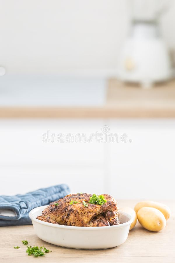 De gehele die kip in witte schotel met ruwe aardappels wordt geroosterd kitched lijst Huisbinnenland op de achtergrond royalty-vrije stock fotografie