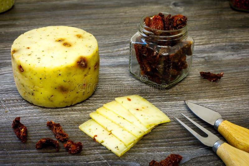De de geitkaas van de landbouwer met droge tomaten, een vork en een kaasmes, a kunnen van droge tomaten op een houten lijst stock afbeelding