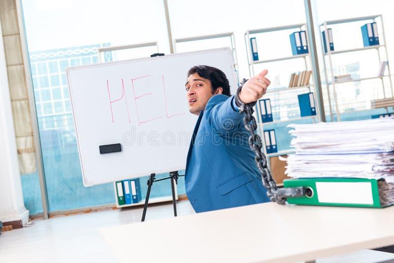 De geketende mannelijke werknemer ongelukkig met het bovenmatige werk stock fotografie