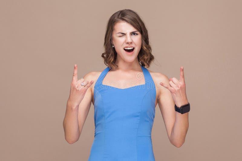 De gekke bedrijfsvrouw toont aan de rots - en - teken rolt stock foto