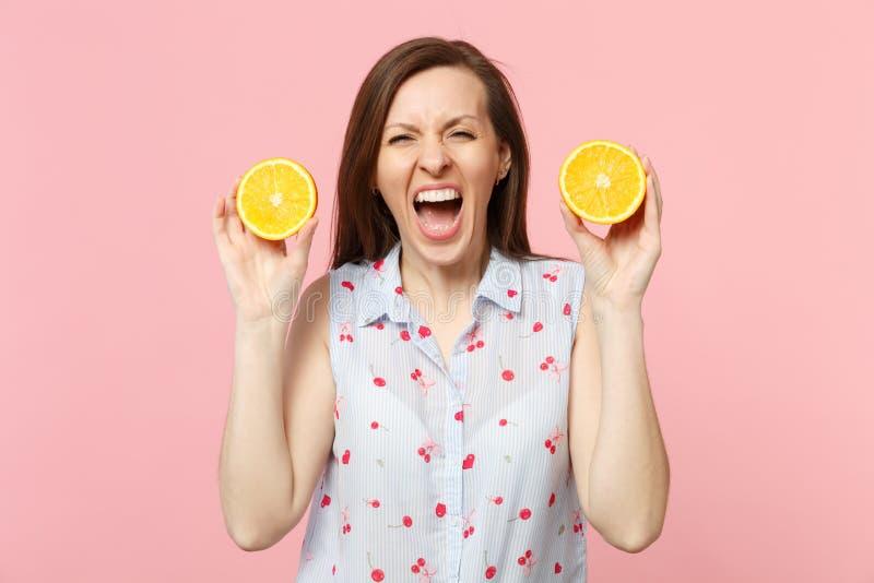 De gekke gillende jonge vrouw in de zomer kleedt het houden van twee halfs van vers rijp oranje die fruit op roze pastelkleurmuur stock foto