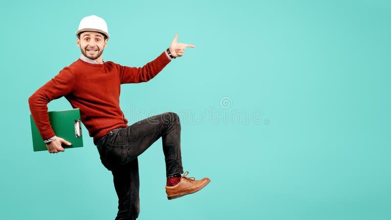 De gekke jonge knappe gebaarde ingenieur of aannemersmens in toevallige uitrusting richt vinger over cyaanachtergrond stock foto