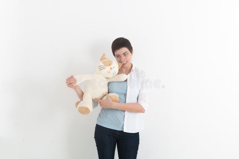 De gekke jonge vrouw bijt een een pluchestuk speelgoed of teddybeer Zachte nadruk royalty-vrije stock afbeeldingen