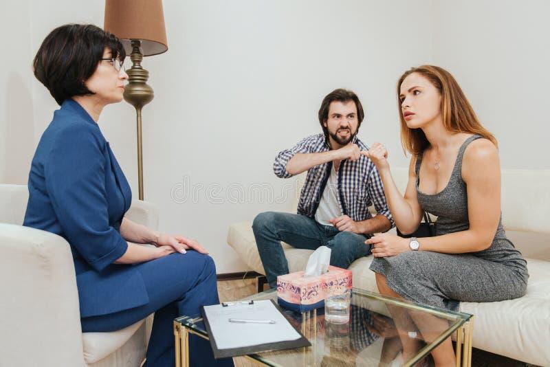De gekke kerel bekijkt zijn vrouw hij haar bedreigt De jonge vrouw bekijkt arts en spreekt aan haar De therapeut is stock fotografie