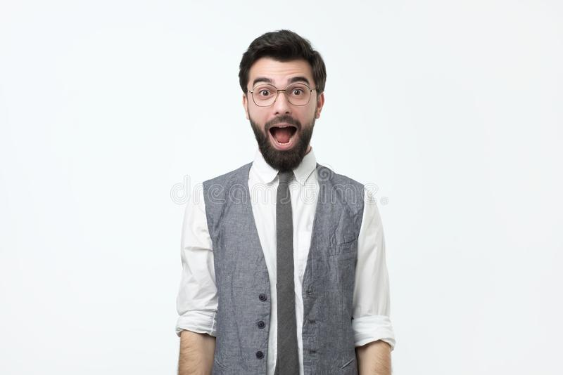 De gekke Spaanse jonge mens met geopende mond is verrast royalty-vrije stock afbeeldingen