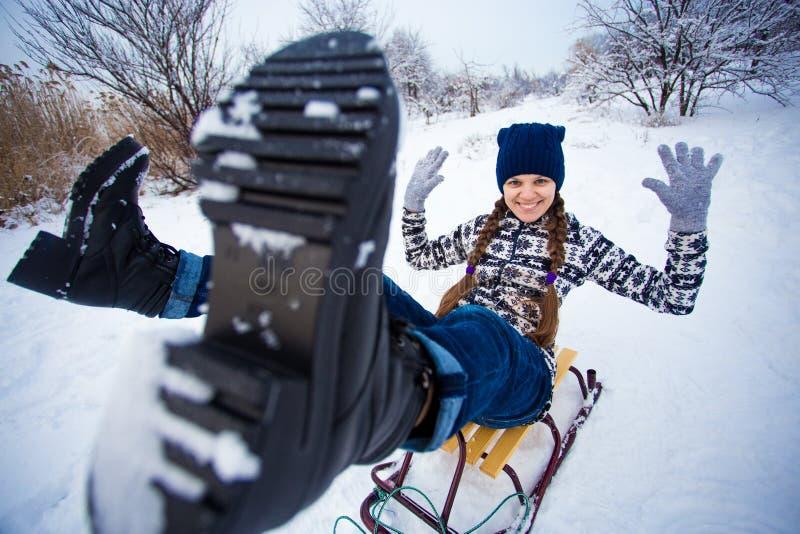 De gekke vrouw geniet van een arrit Vrouw het sledding stock foto