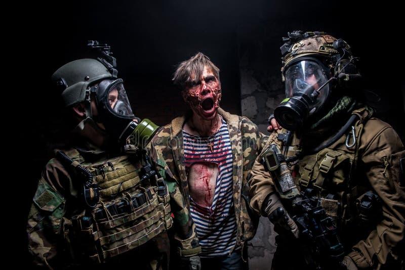 De gekke zombie valt twee militairen met kanonnen aan stock foto