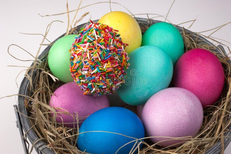 De gekleurde die paaseieren en één worden behandeld met bestrooien in geïsoleerd nest royalty-vrije stock afbeelding