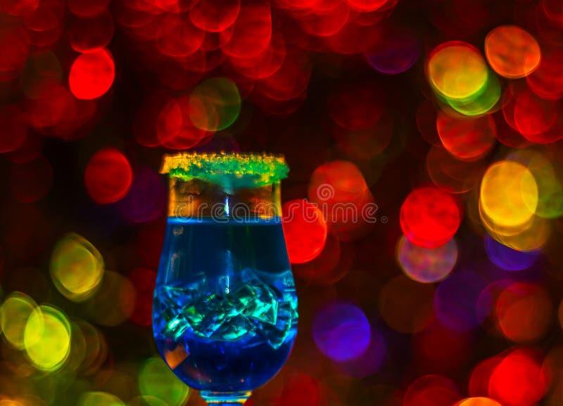 De gekleurde drank in glas, cocktail, nacht steekt bokeh achtergrond aan royalty-vrije stock fotografie
