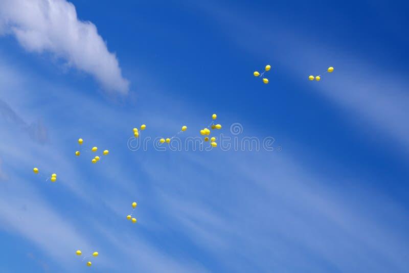 De gekleurde en multi-colored gelballons vliegen in een groep heldere blauwe hemel royalty-vrije stock afbeelding