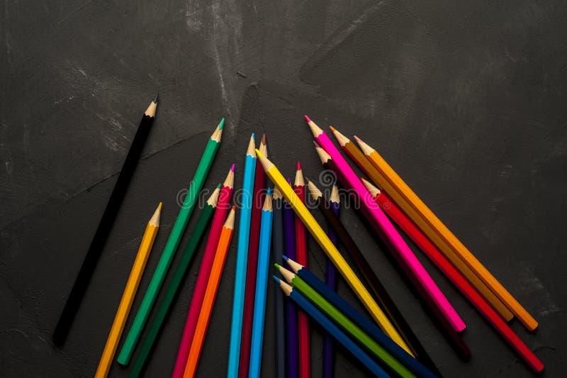 De gekleurde gescherpte potloden liggen op de donkere oppervlakte royalty-vrije stock afbeeldingen