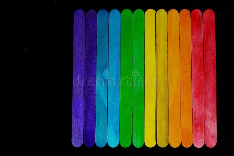 de gekleurde houten bar in spectrumtoon rangschikken op zwarte achtergrond en de ruimte die voor schrijven verwoording, in modern royalty-vrije stock fotografie