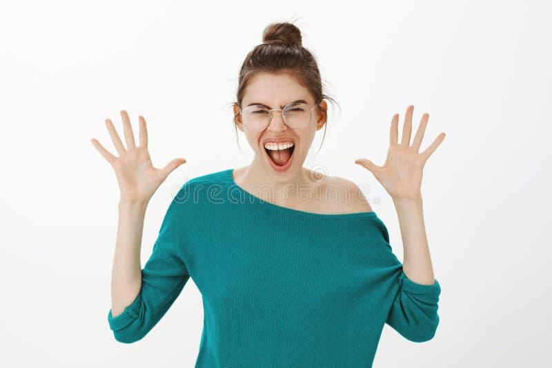 De gekomen stijl van jazzhanden nooit uit Portret van blije onbezorgde Kaukasische vrouw in eyewear en losse sweater, het schreeu stock foto