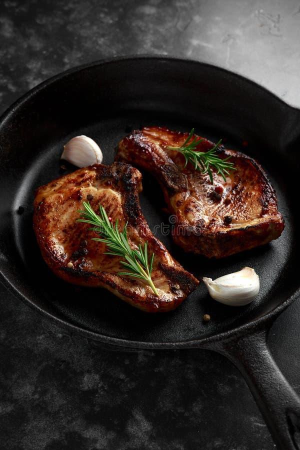 De gekookte karbonades van het Varkensvleeslendestuk in rustieke koekepan, pan met rozemarijn Hoogste mening Achtergrond royalty-vrije stock afbeelding
