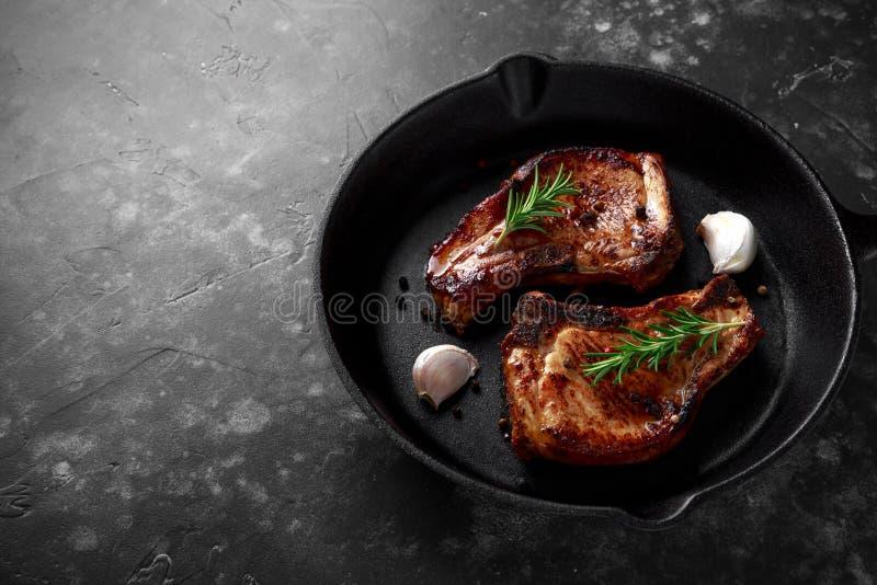 De gekookte karbonades van het Varkensvleeslendestuk in rustieke koekepan, pan met rozemarijn Hoogste mening Achtergrond royalty-vrije stock foto