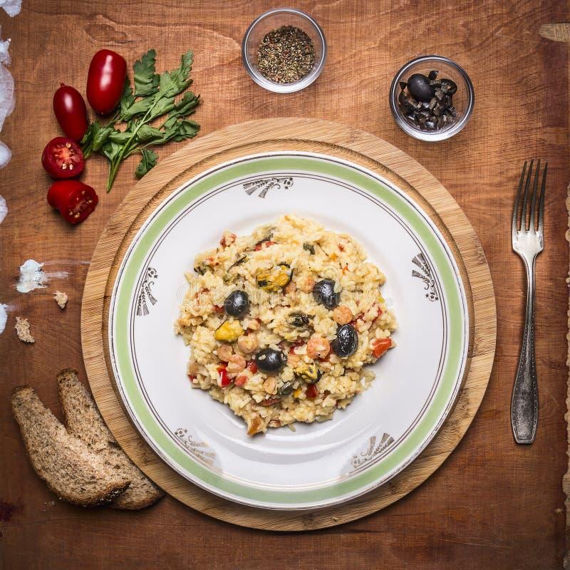 De gekookte paella met zeevruchtenschotel op een hakbord met brood kruidde met kruiden en tomaten een vork op rustieke houten bac royalty-vrije stock afbeeldingen