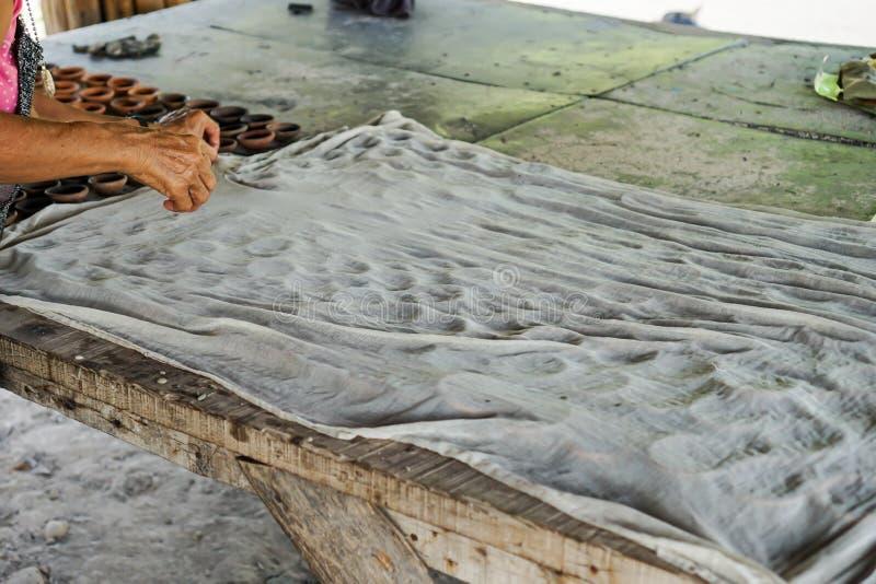 De gekookte suiker van suikerpalm giet neer op aardewerkkop Behandeld met witte doek stock fotografie