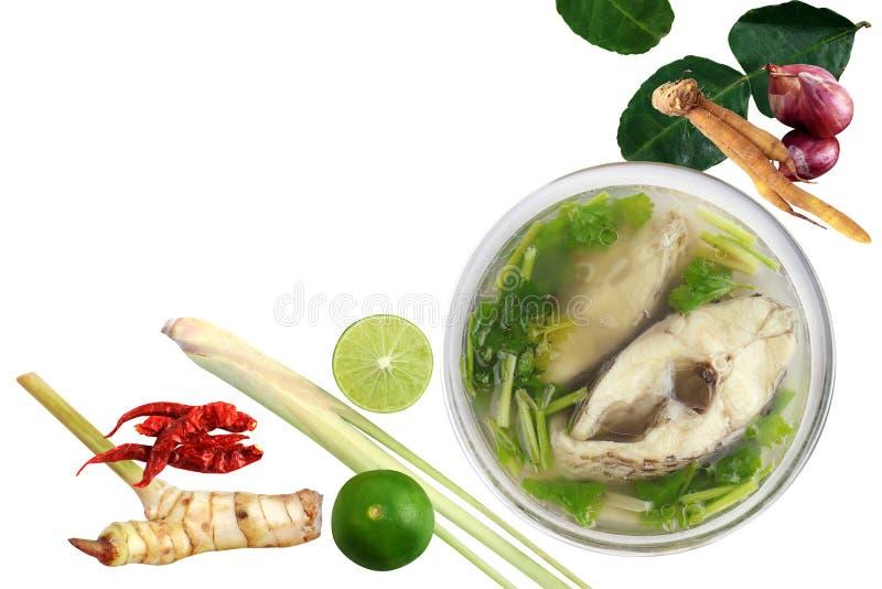De gekookte tilapia vissen in duidelijke kom en de Ingrediënten kruiden op witte Tom-yam-Pla als achtergrond Thais woord, kruidig stock foto