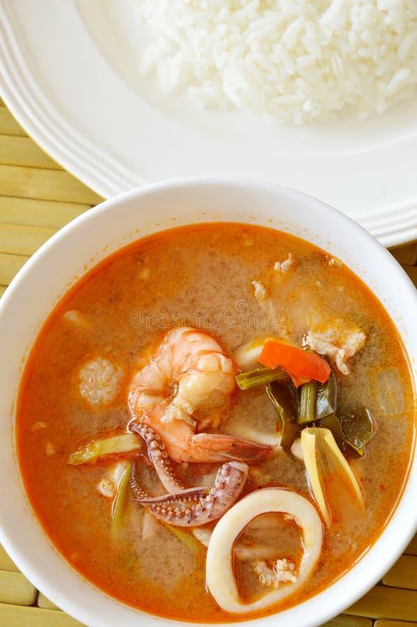 De gekookte zeevruchten en varkensvleestom yum Thaise kruidige soep eet met rijst stock foto's