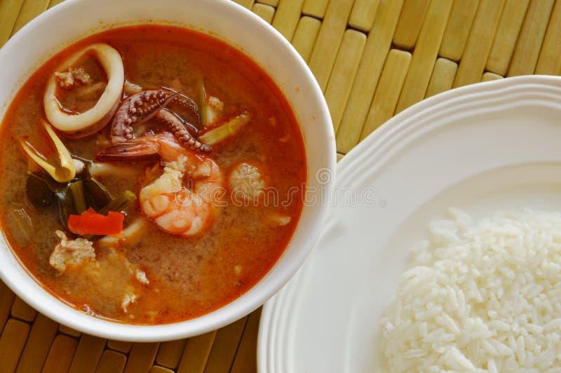 De gekookte zeevruchten en varkensvleestom yum Thaise kruidige soep eet met rijst stock afbeelding