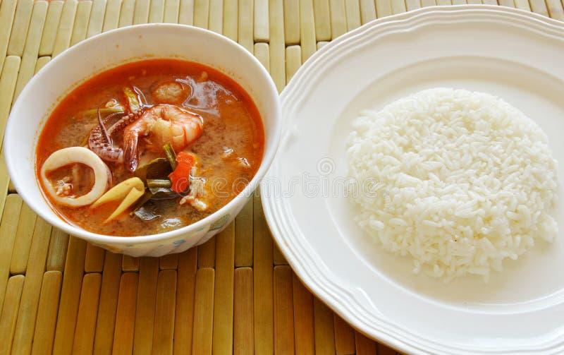 De gekookte zeevruchten en varkensvleestom yum Thaise kruidige soep eet met rijst stock foto